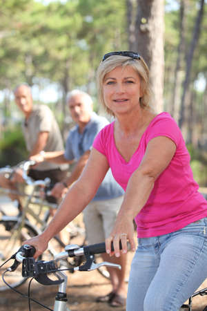 Woman riding a bike with friends in a forest