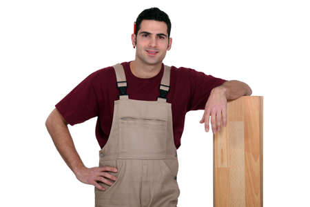 Man standing next to a wooden plank