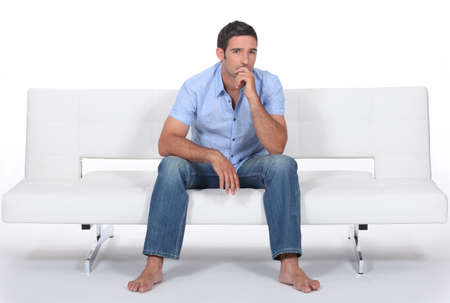 barefoot man sitting on a modern couch and wondering