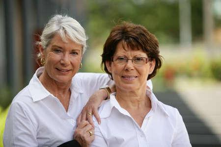 Two older women standing outside