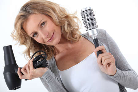 Woman holding a hair dryer and brush