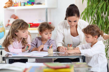 Photo pour Woman helping a group of girls with their homework - image libre de droit