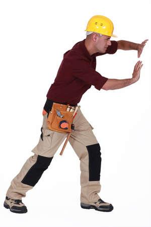 Tradesman pushing an invisible wall