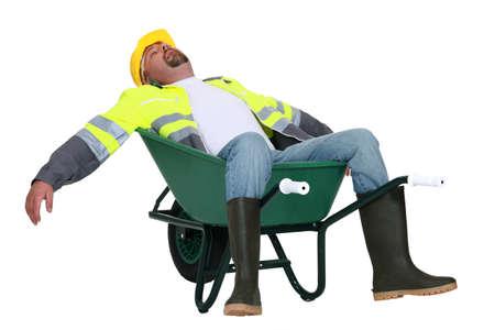 Tradesman asleep in a wheelbarrow