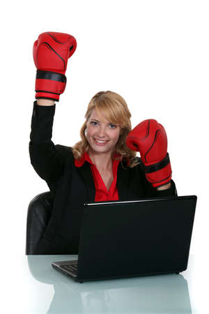 Woman wearing boxing gloves whilst sat at deskの写真素材