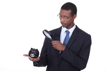 African man looking at a piggy bank through a magnifying glass