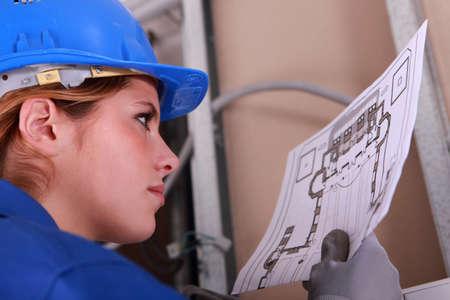 Female electrician reading diagram