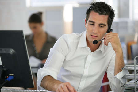 Young man telemarketer in call center
