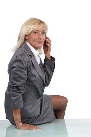 Senior businesswoman perched on desk during call