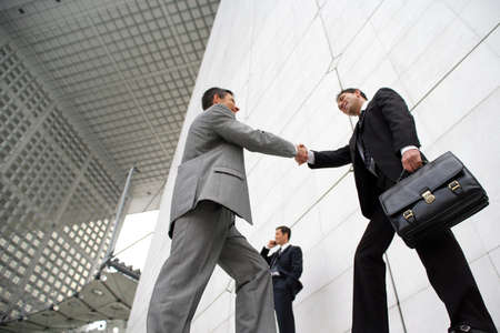 Businessmen shaking hands outside