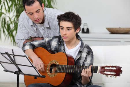 Photo pour Adolescent boy learning to play the guitar - image libre de droit