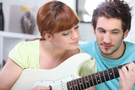 Man teaching a woman to play the guitar
