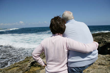 Retired couple staring out over the ocean