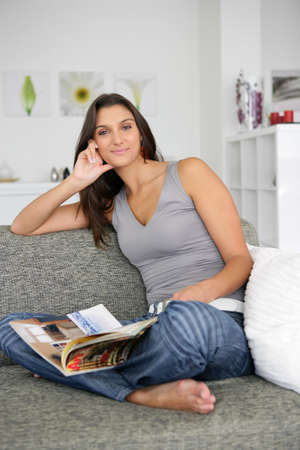 Woman sat at home reading magazine on couch