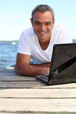 Man using his laptop on a wooden jetty