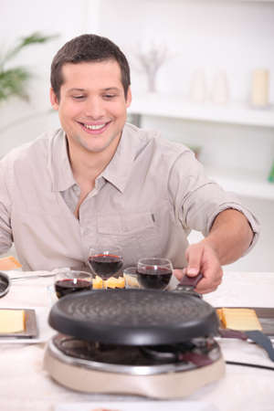 Man enjoying raclette at home with friends
