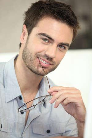 Man biting his glasses