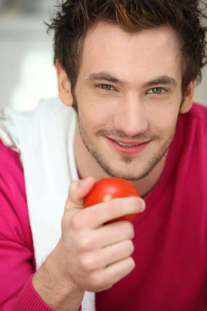 Portrait of a man holding a tomato