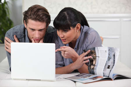 Couple looking at a brochure and a laptop