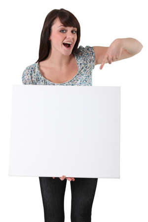 young woman pointing at a blank boardの写真素材