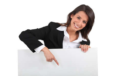 Businesswoman pointing at sign