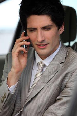 Businessman making phone call in his car