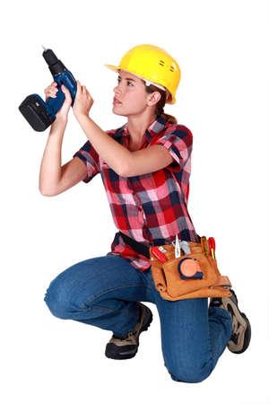 Woman carpenter using screwdriver