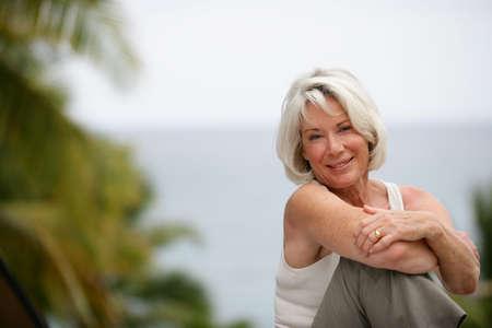 Foto für Elderly woman enjoying a day out by the lake - Lizenzfreies Bild