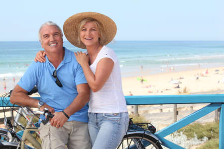 Mature couple with bikes by the beach