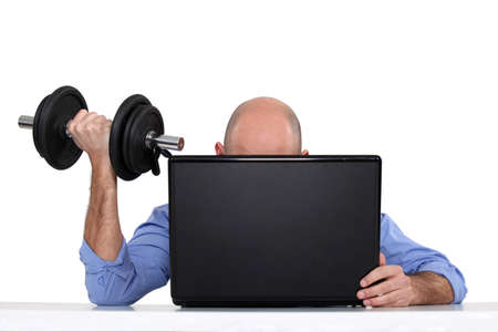 Businessman using weights at his desk