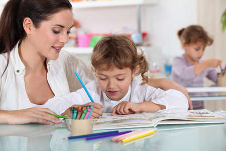 Woman and child colouring at a desk