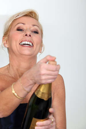 Cheerful woman opening bottle of champagne