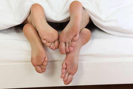 Photo pour Bare feet under a duvet - image libre de droit