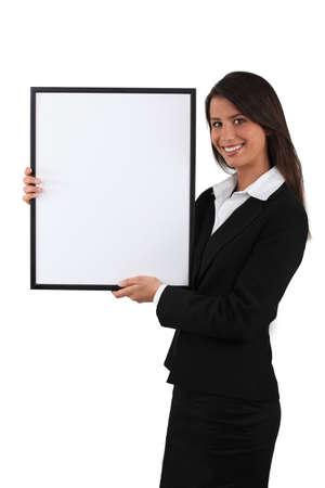 Businesswoman holding white board
