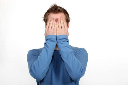 Man covering his face in shame