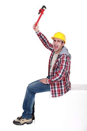 Angry tradesman holding a pipe wrench