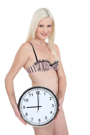 Woman in her underwear with a clock showing 9 00