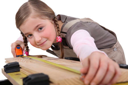 a child girl measuring a plank