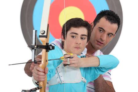 Boy having archery lesson