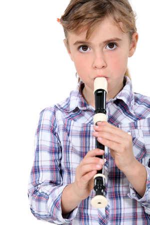 Photo pour Little girl playing a recorder - image libre de droit