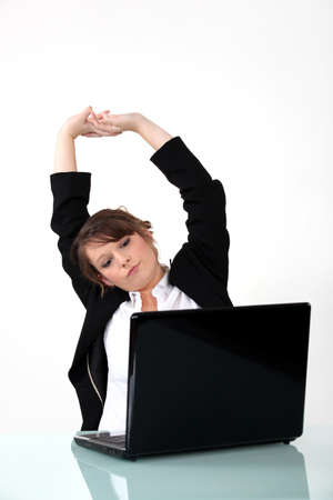 Businesswoman sat at desk stretching