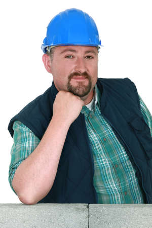 Builder proudly standing by wall