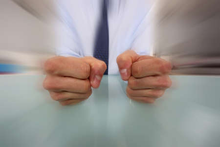 Businessman banging his fists on his desk