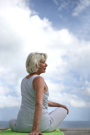 Senior woman doing yoga outdoors