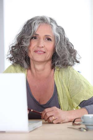 Foto für Gray-haired woman in front of laptop computer - Lizenzfreies Bild