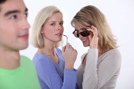Photo pour Women checking out a young man - image libre de droit