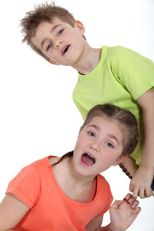 Young boy pulling his sister