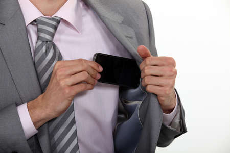 Businessman putting his mobile phone into his pocket