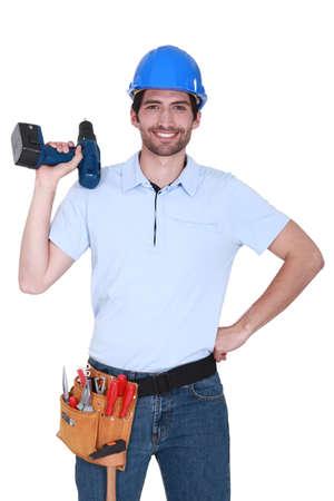 Photo pour happy craftsman holding a drill - image libre de droit