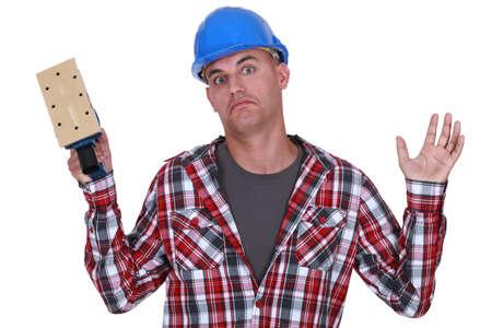 Construction worker holding up a sander